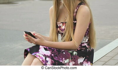 Young girl with a cellphone outdoors - Young girl sitting in...