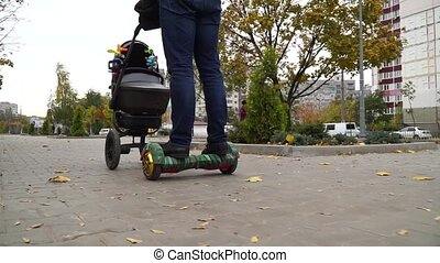 Gyroscooter's and baby carriage's wheels rolling on the sidewalk