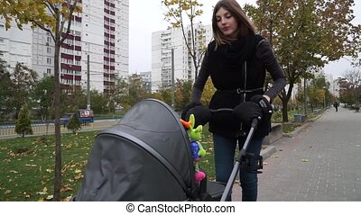 Woman caring for a child in a pram while walking