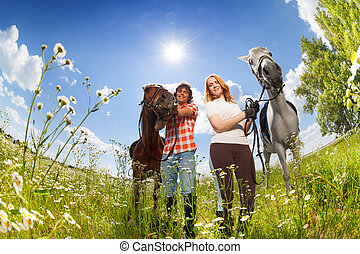 Portrait of young couple with purebred horses