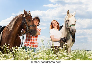 Young happy couple with their purebred horses