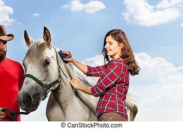 Young woman grooming the mane of her white horse - Happy...