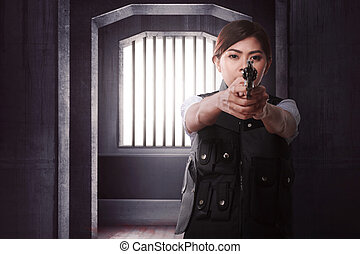 Beautiful asian woman with gun standing alone on dark room