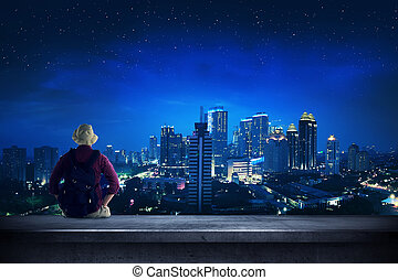 Traveler sitting on the rooftop watching city at night