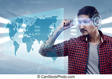 Young man looking world map with futuristic smart high tech glasses