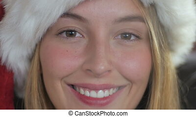 Close up of a young attractive woman in a Santa hat drinking hot tea