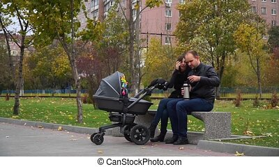 Family in autumn park drinking tea from a thermos