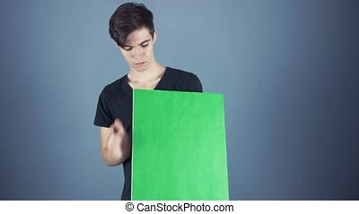 Young man in black shirt holding green key sheet poster gray background
