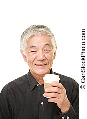 senior Japanese man takes a coffee break - studio shot of...