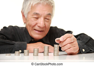 senior Japanese man put coins to stack of coins - studio...
