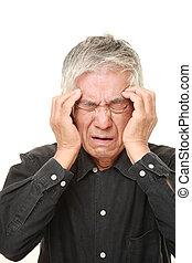 senior Japanese man suffers from headache - studio shot of...