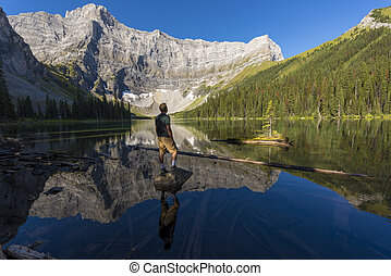 Young man standing on a rock in lake looking up at mountains