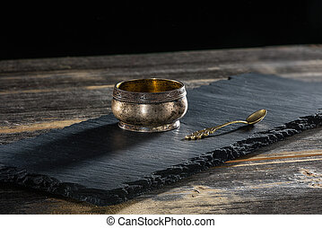 Ancient melkhiorovy saltcellar with spoon on a black slate...