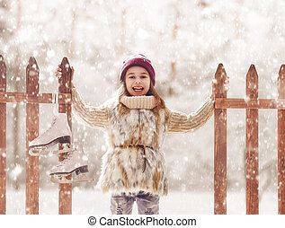 girl is going skate - Happy child playing on a winter walk...