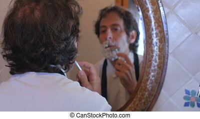 A man getting ready for work checks his watch and runs out with a half a beard