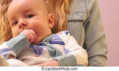 Close-up of baby chews her fingers while sitting on hands at mum