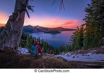 Tourist looking at Crater Lake Oregon Landscape - Backpacker...