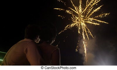 young couple looking at the beautiful fireworks