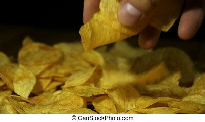Potato Chips Rotating On Black Background in Slow Motion -...