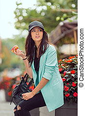 Young asian woman eating fast food outdoors