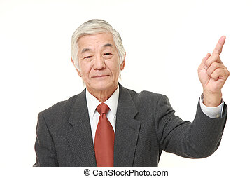 senior Japanese businessman presenting and showing something...