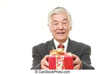 senior Japanese businessman offering a gift - senior...