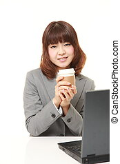 Japanese businesswoman takes a coffee break - studio shot of...