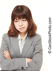 young Japanese businesswoman in a bad mood - studio shot of...
