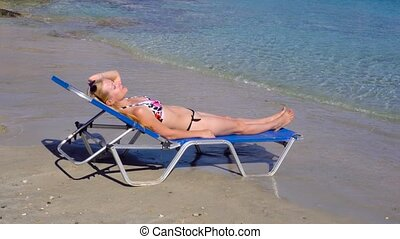 woman laying in sunbed on beach - young woman laying in...