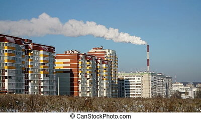 The smoke from the chimney of the plant on the residential area. The urban ecology.