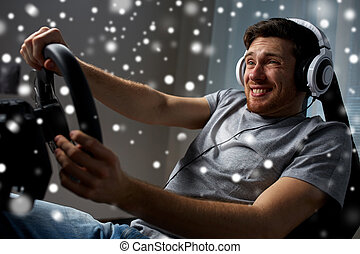 man playing car racing video game at home - technology,...