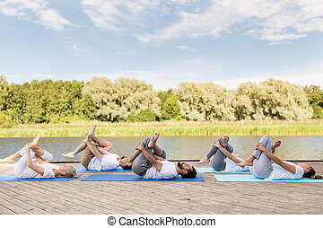 people making yoga in supine pigeon pose outdoors - yoga,...