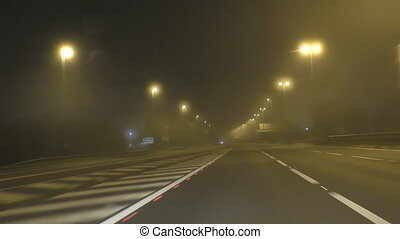 Fog on motorway at night - Windshield view while driving on...