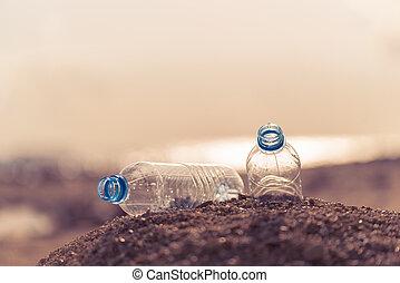 Plastic waste bottles on sandy ground