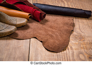 Leather in rolls and shoe lasts on wooden background....
