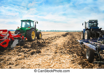 Two tractors in a field. - Two tractors with a plow in a...
