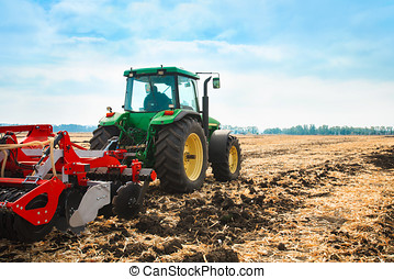 Tractor with a harrow in the field. - Tractor with a harrow...