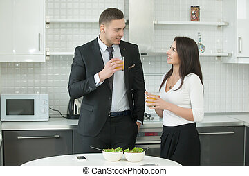 Man and woman drinking juice at the kitchen