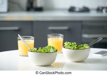 Two bowls of salad and glasses of orange juice on a white...