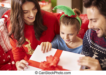 Family with little girl opening Christmas present