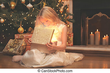happy child opens the magic box gift with light in dark over christmas tree and fireplace at home