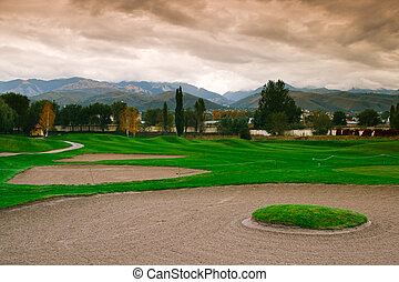 Game in the golf club against the mountains and dramatic sky