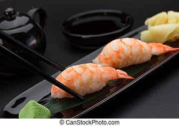Shrimp sushi nigiri on a black plate over dark background