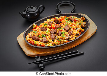 Japanese cuisine. Rice with veal over black background.