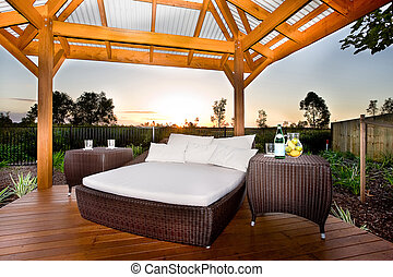 Bed in outside area like a patio or relaxing place of a modern house or a hotel at sundown