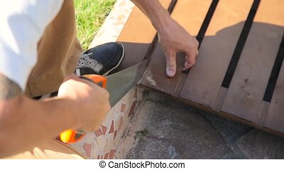 man sawing a board close up