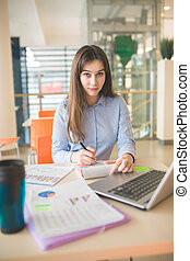 Working hard - Portrait of young woman working at cafe on...