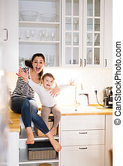 Mother with daughter in the kitchen sitting on countertop