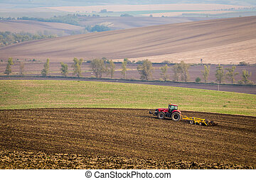 Red tractor plows the field in autumn.