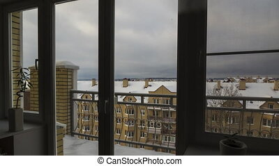 Winter view from the window to snow covered roofs. Day to night 4K timelapse